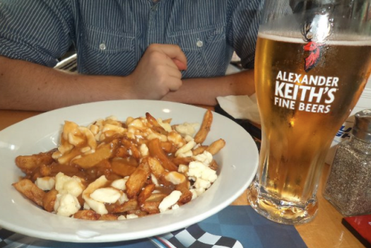 Enjoying the typical cuisine of Québec: the poutine (fries with cheese and a brown secret sauce) next to a local beer // Disfrutar de la cocina típica de Québec: la poutine (papas fritas con queso y una salsa secreta) al lado de una cerveza local - Picture by Andrea Arzaba